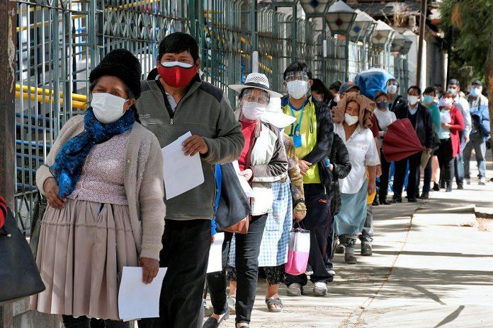 personas hacen fila para vacunarse