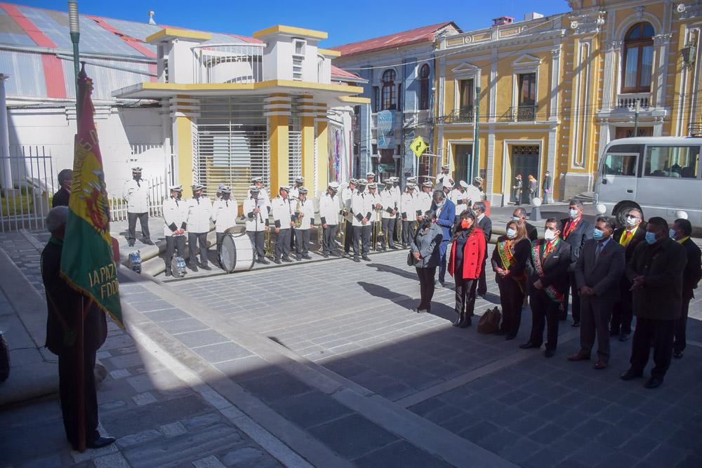 Iza de la bandera junto a la banda Eduardo Cava